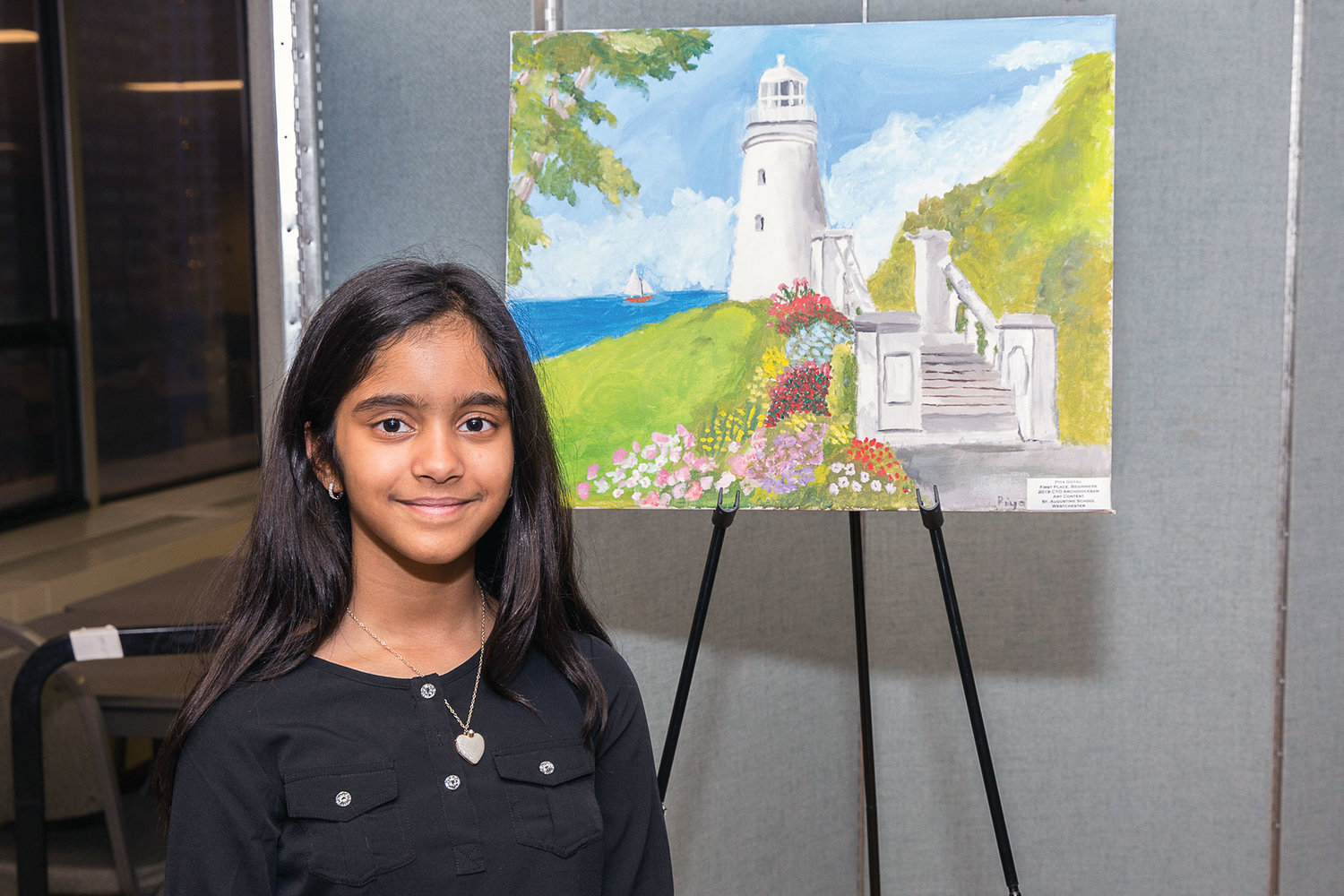 Piya Goyal, a fourth-grader at St. Augustine School in Ossining, poses with her first-place painting for third- and fourth-graders.