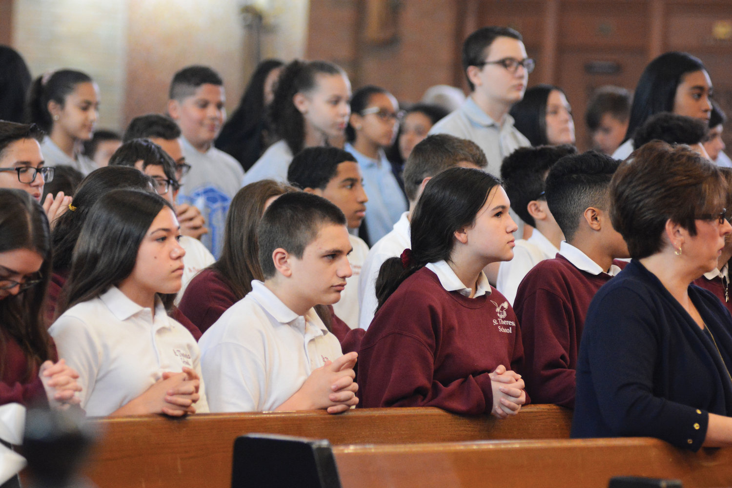"During the Mass, students pray. ""And now you are part of that legacy,"" the cardinal told the students about joining the proud multitudes who have graduated from archdiocesan elementary schools."
