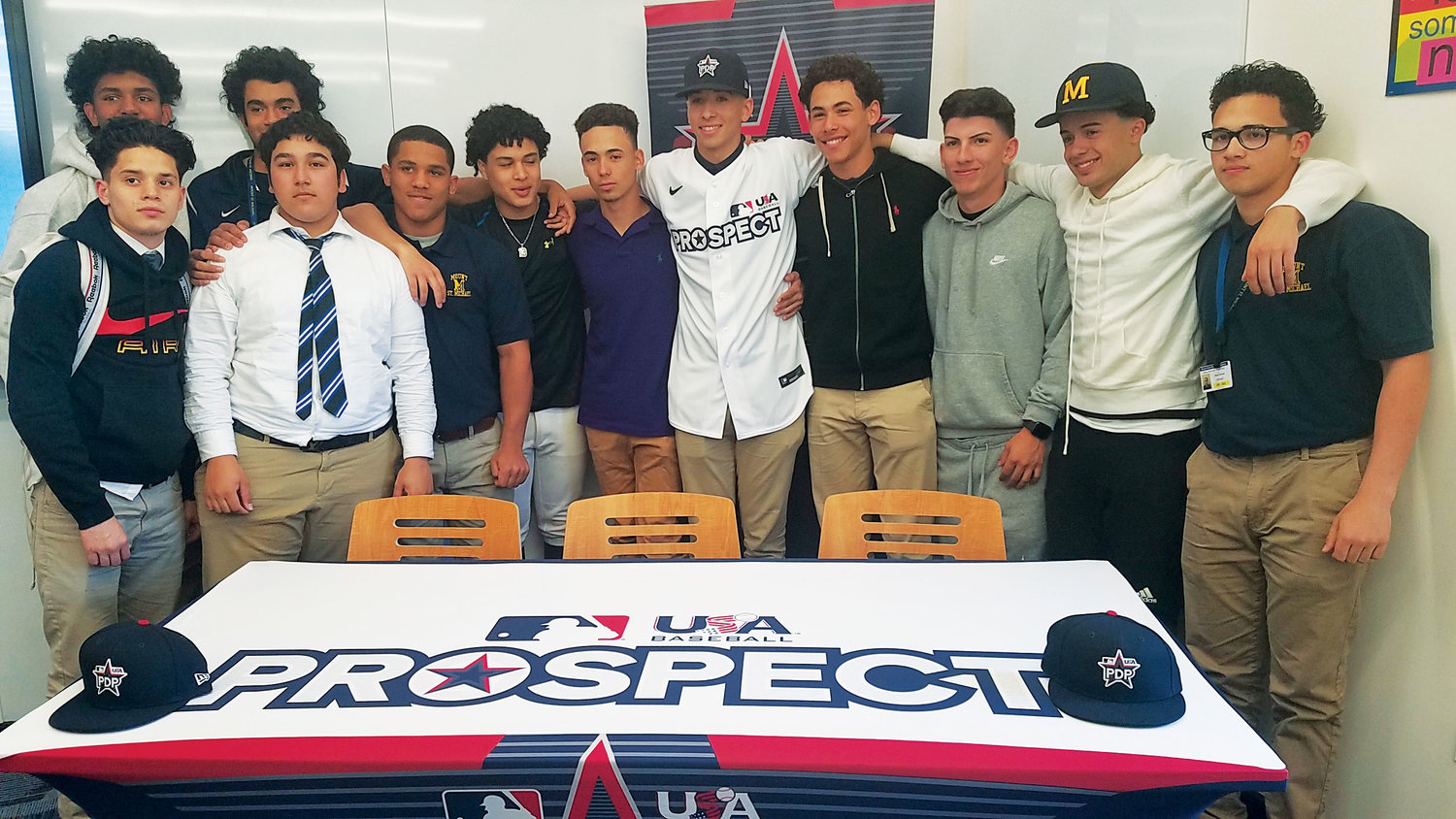 OFF TO CAMP—Alex Santos, center, joins his Mount St. Michael Academy teammates after being presented his jersey and cap for the inaugural Prospect Development Pipeline League in a ceremony May 16 at the Bronx school.
