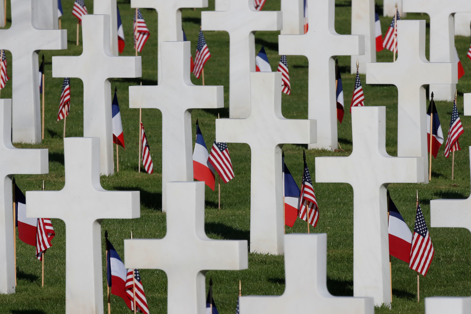 American and French flags are seen in front of headstones in the cemetery of Colleville-sur-Mer in Normandy, France, June 6.