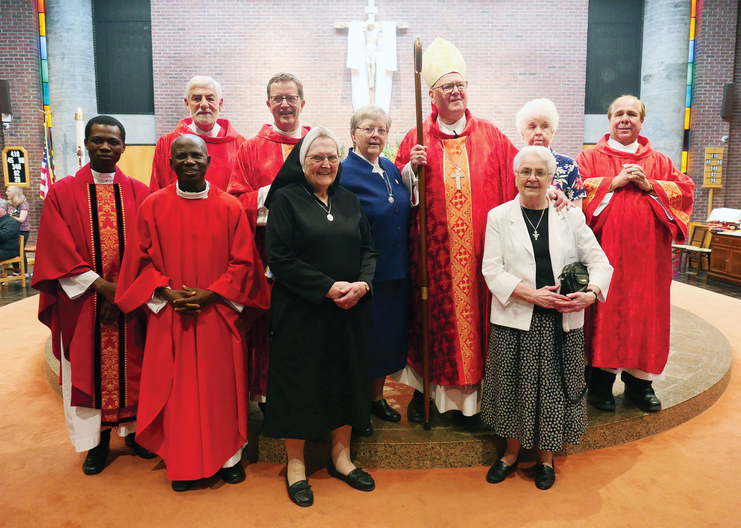 Cardinal Dolan joins, from left, Father John Kwaku Sah, parochial vicar; Father Andrew Amankwaa; Deacon Anthony Ferraiuolo; Father Rees Doughty, pastor; Sister Mary McCaffrey, O.S.F.; Sister Helen Hofmann, O.S.F.; Sister Barbara Ann Sansone, O.S.F.; Sister Rose Jerome Kenlon, O.S.F.; and Deacon Lenny Farmer. The Orange County parish is awaiting approval for a name change to St. Marianne Cope.
