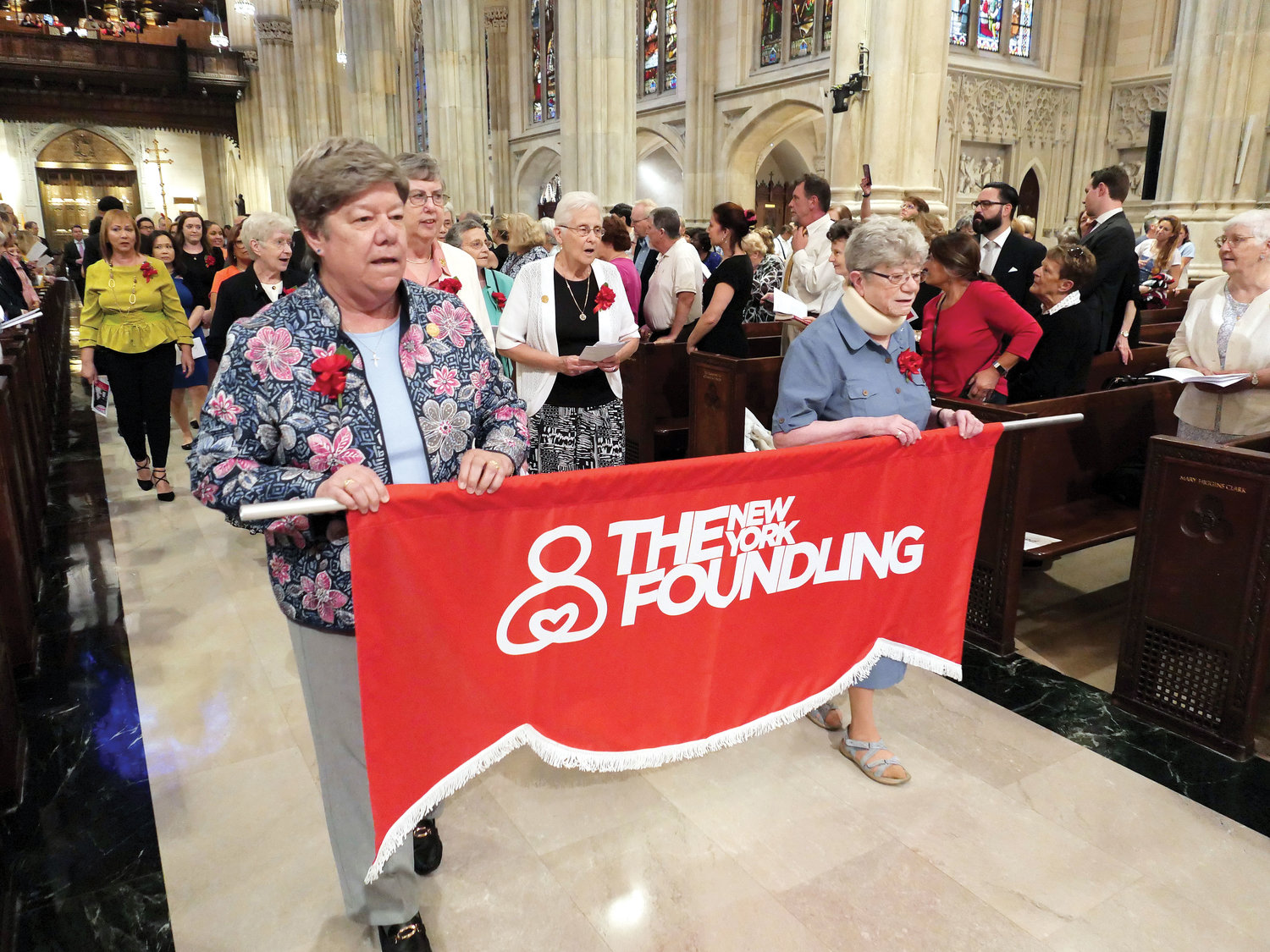 Sisters of Charity Donna Dodge, S.C., left, and Jane Iannucelli, S.C., carry a banner in procession for a Mass Cardinal Dolan celebrated in honor of the New York Foundling's century and a half of service June 6 at St. Patrick's Cathedral.