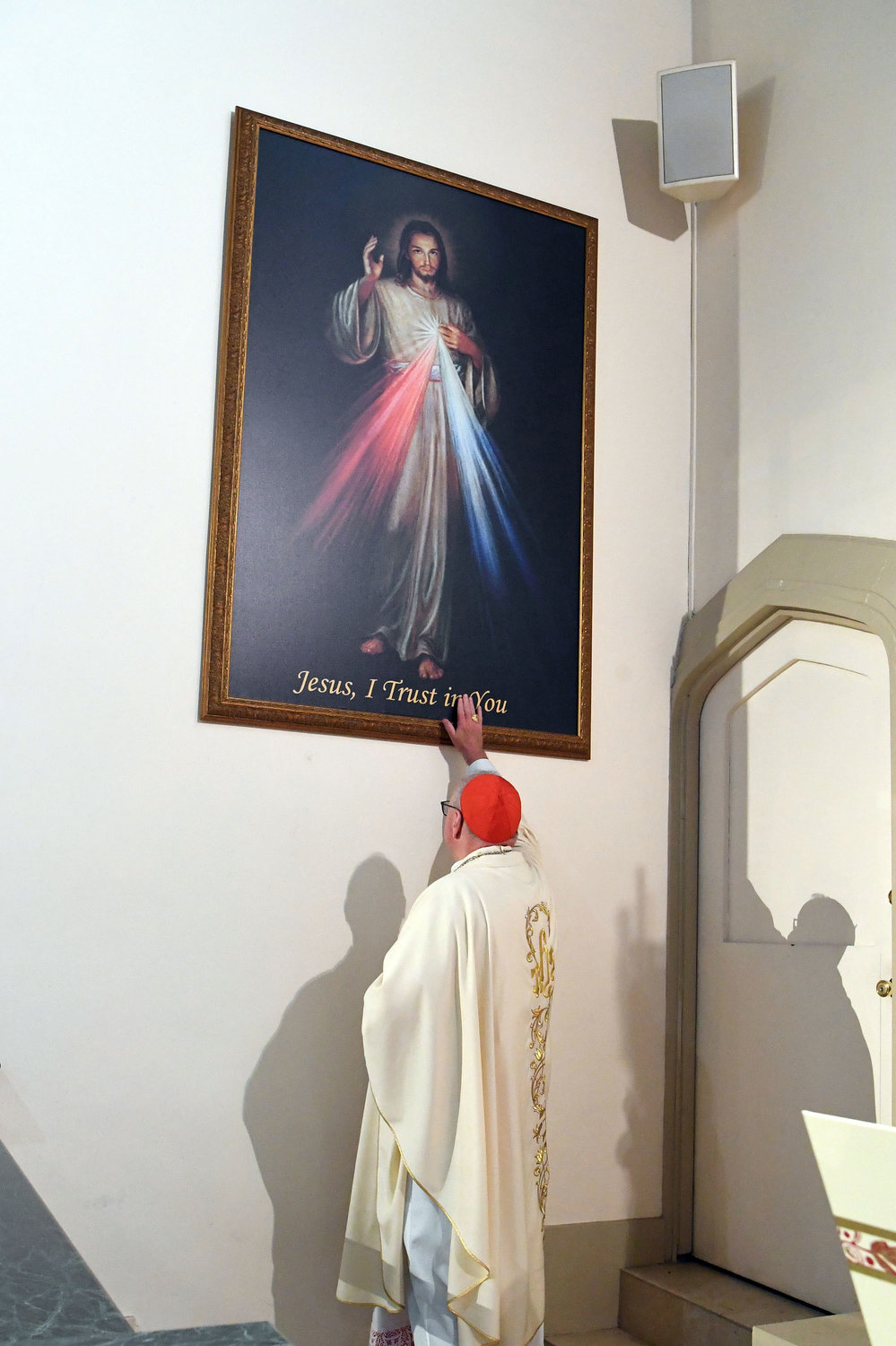 Cardinal Dolan touches the newly blessed image of the Divine Mercy at Our Lady Queen of Peace Church on Staten Island June 23.