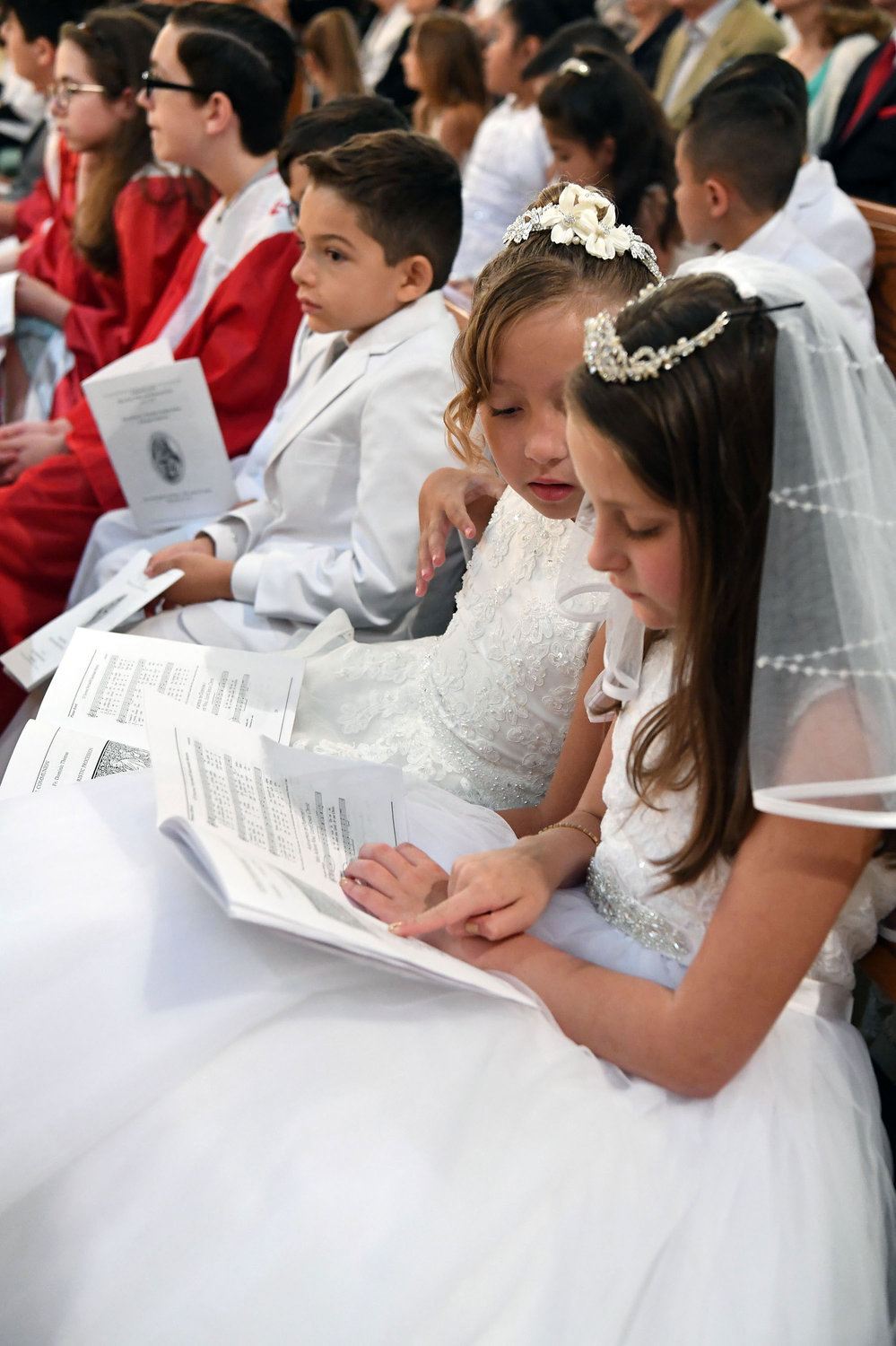 Sophia Marin and Quinn Tycenski are among the first Holy Communicants attending the Mass.
