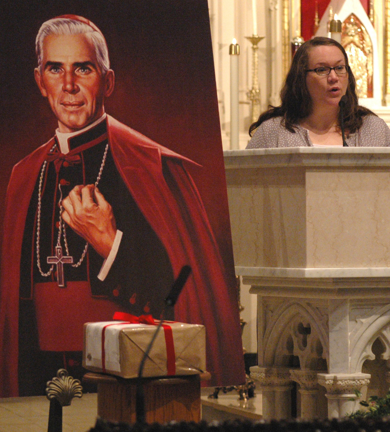 With evidence of her son's alleged miraculous healing boxed and sealed in front of a portrait of Archbishop Fulton J. Sheen, Bonnie Engstrom delivers a reading during Mass at St. Mary's Cathedral in Peoria, Ill., Dec. 10, 2011. On July 5 of this year, Pope Francis formally approved the miracle attributed to the intercession of Archbishop Sheen, moving him one step closer to beatification.