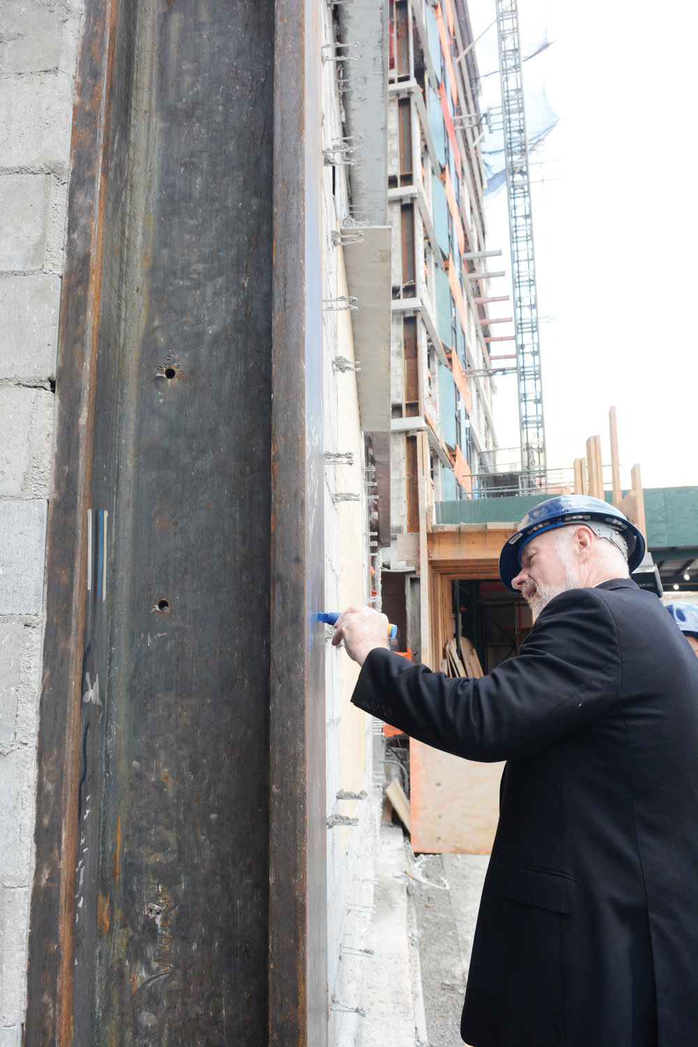 Msgr. Kevin Sullivan, executive director for Catholic Charities in the archdiocese, signs a building beam.