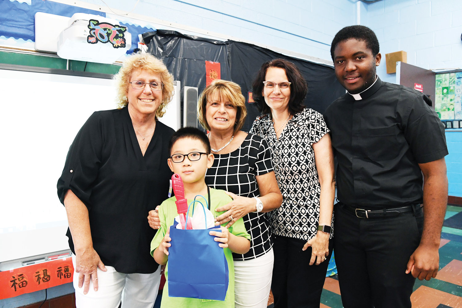 Sam Lin Gaoxi, 8, pictured with camp director Mary Lee, principal Theresa Signorile, assistant principal Denise Olsen and Collins Ashu, a seminarian at St. Joseph's Seminary, Dunwoodie.