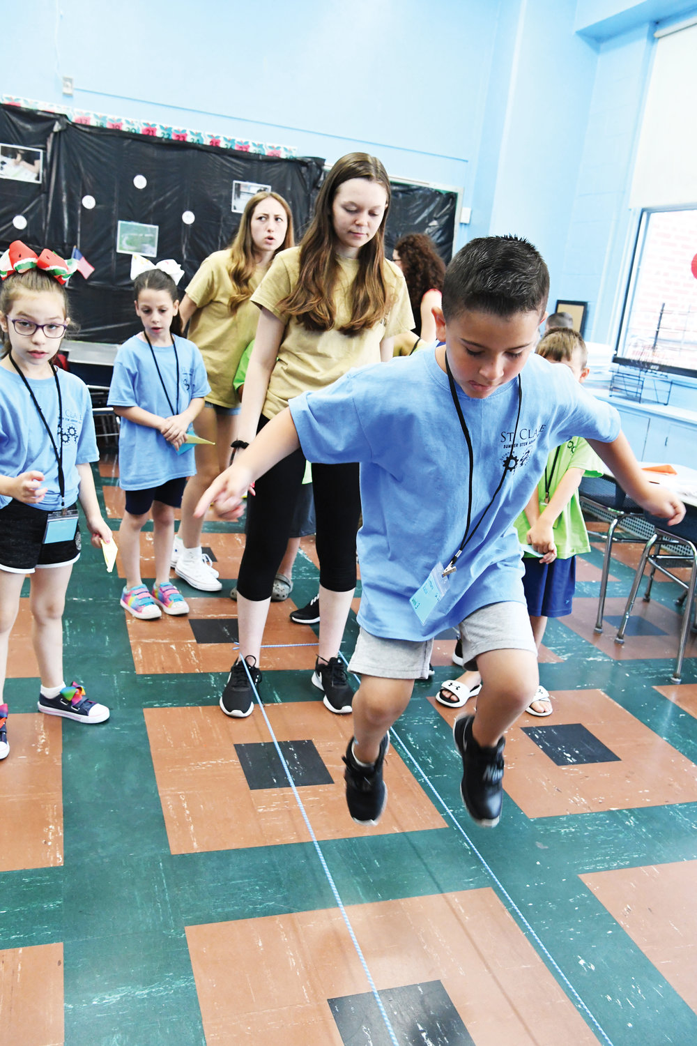 Second-grade camper Anthony Russo participates in a Chinese jump rope game, and behind him is camp counselor Bethany Werth.