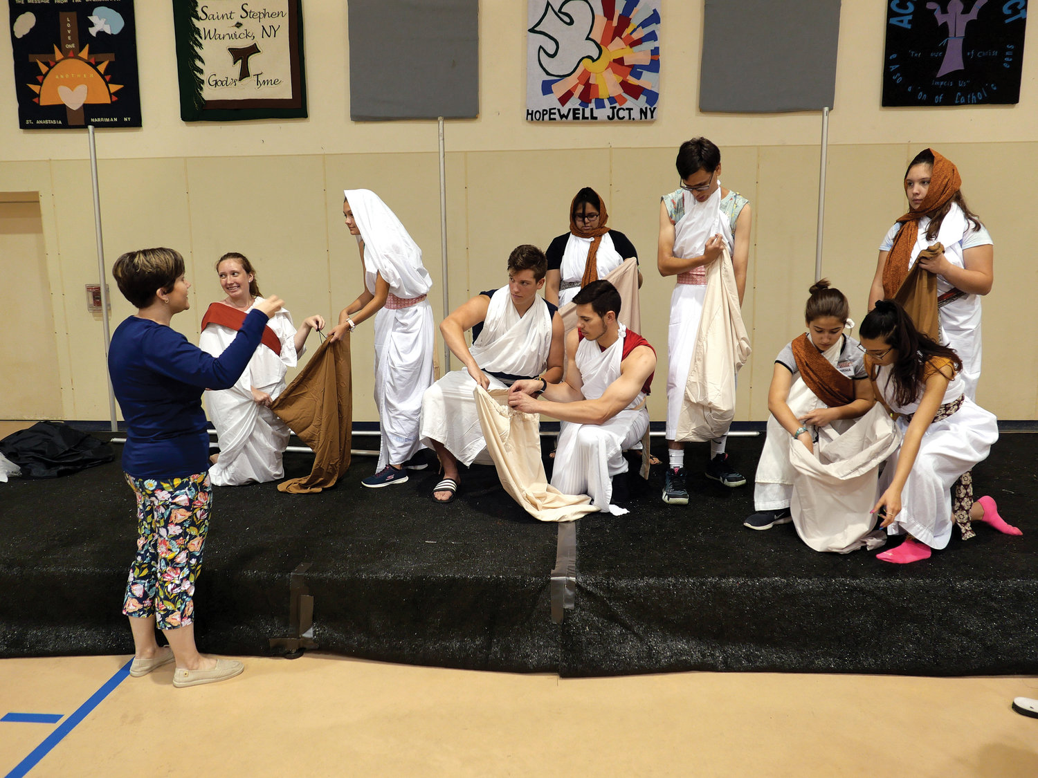 "Director Emilia Lynch speaks with Catholic Literature and Arts Summer Program campers on stage during a July 29 rehearsal for ""Ruth: A Musical Witness to Love"" in the St. Genesius Gymnasium on the campus of Capuchin Youth & Family Ministries in Garrison."