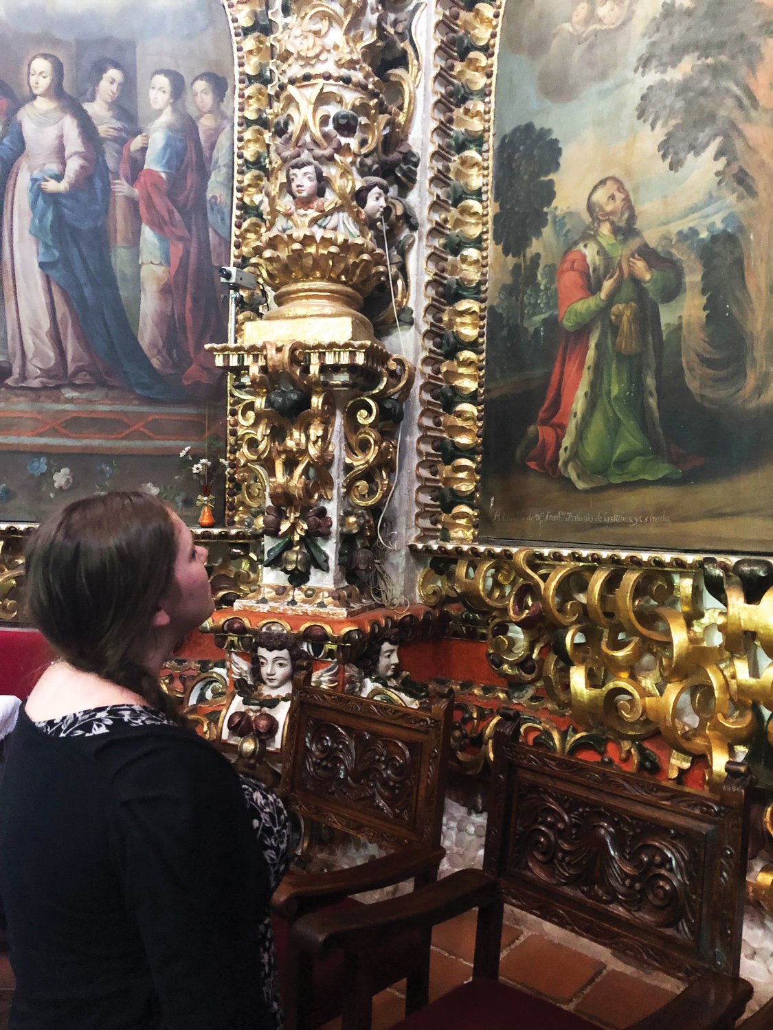 Ms. Colgan reflects before religious paintings inside the Basilica of Our Lady of Ocotlan, in Ocotlan, Tlaxcala, Mexico.