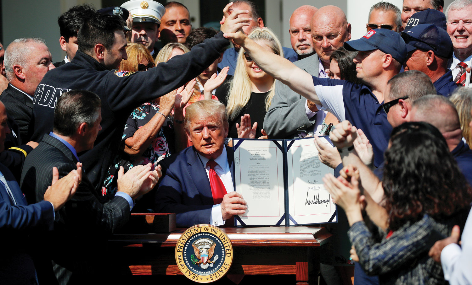 "New York City first responders celebrate as President Donald Trump displays the ""Permanent Authorization of the September 11th Victim Compensation Fund Act"" during a signing ceremony in the White House Rose Garden in Washington, D.C., July 29. Trump signed H.R. 1327 into law, making the compensation fund essentially permanent. It took nearly 18 years to get the legislation passed to benefit anyone sickened or dying from the fallout of the 9/11 terrorist attacks."