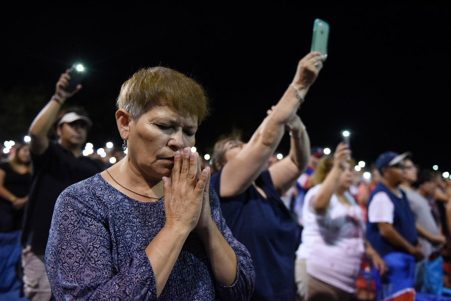 A woman prays during an Aug. 4 vigil, a day after a mass shooting at a Walmart store in El Paso, Texas.
