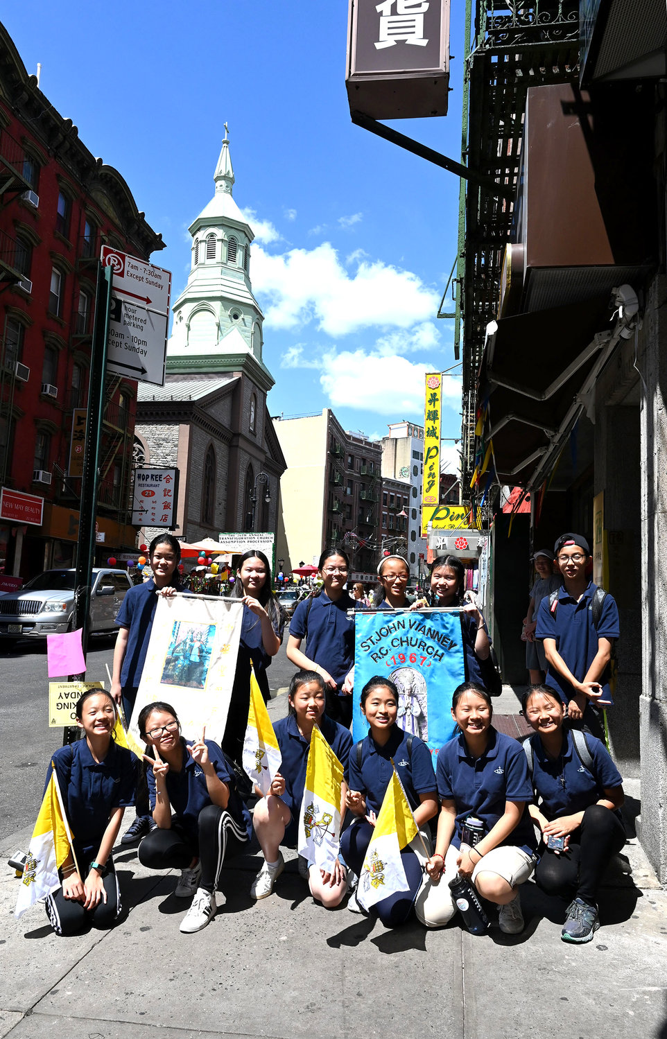 Young adults hold banners from Our Lady of China Chapel in Elmhurst, Queens, and St. John Vianney parish in Flushing, Queens.