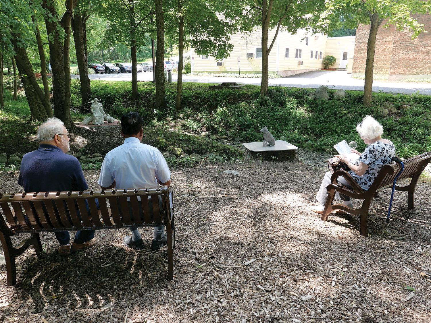 Parishioners sit in the St. Francis Prayer Garden, one of two new outdoor shrines blessed and dedicated at St. Elizabeth Ann Seton parish in Shrub Oak Aug. 11. The garden is a project of the parish's Portiuncula Fraternity of the Secular Franciscan Order.