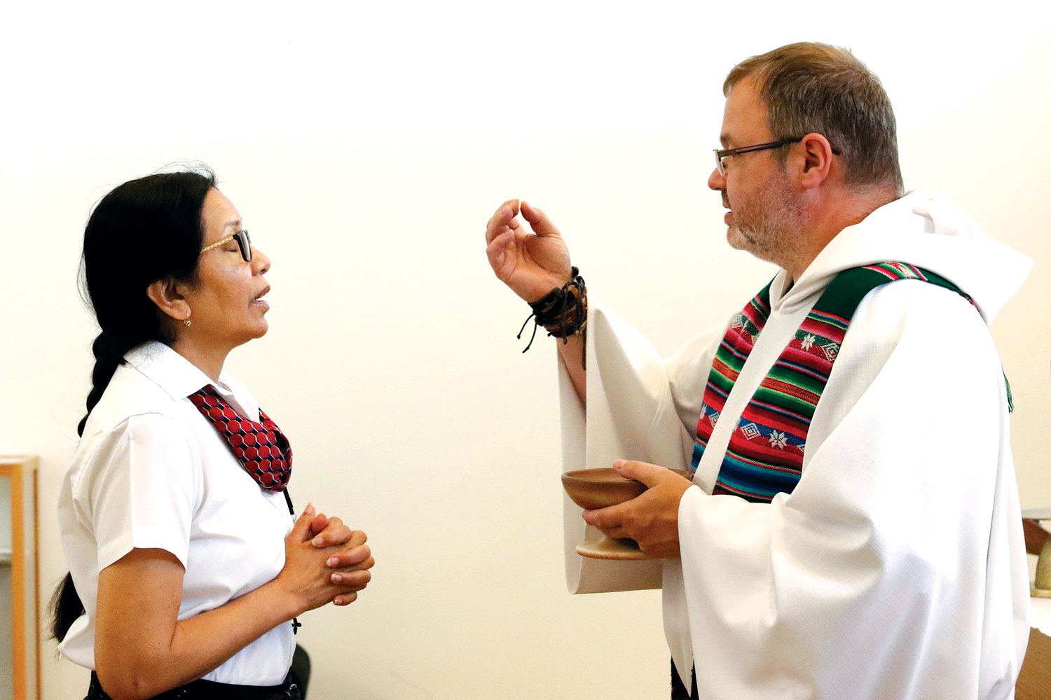 Father Chris Piasta, Catholic chaplain at John F. Kennedy International and LaGuardia airports in Queens, distributes Communion to security guard Teresa Rampersad during Mass at JFK's Our Lady of the Skies Chapel Aug. 5.