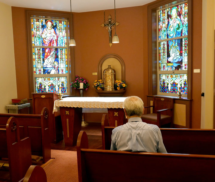 TRAVELERS WELCOME—The Leo House, a Catholic guesthouse in the Chelsea section of Manhattan, has been a haven for visitors for 130 years. A man reflects inside the Leo House chapel.