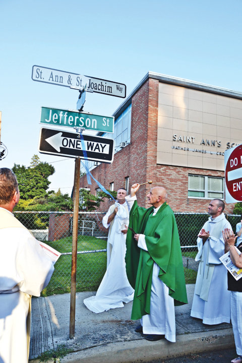 Father George Torok, C.O., weekend assistant, blesses the new street sign unveiled by Father Roman Dominik Palecko, C.O., assistant pastor, renaming Jefferson Street near St. Ann Church in Nyack to St. Ann and St. Joachim Way July 27. The street is named after the parents of Mary and grandparents of Jesus. A Mass and the street renaming kicked off the 150th anniversary year at the church, which is part of St. Paul and St. Ann parish.