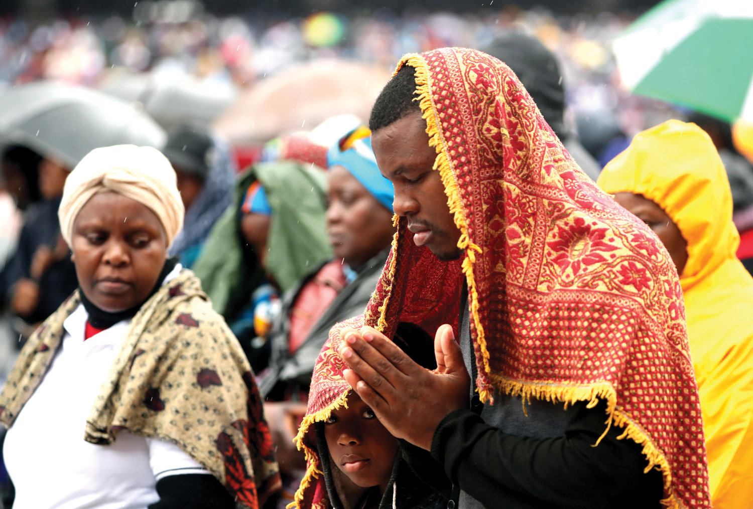 A man prays alongside a child as the pope celebrates Mass in Zimpeto Stadium outside Maputo, Mozambique, Sept. 6.