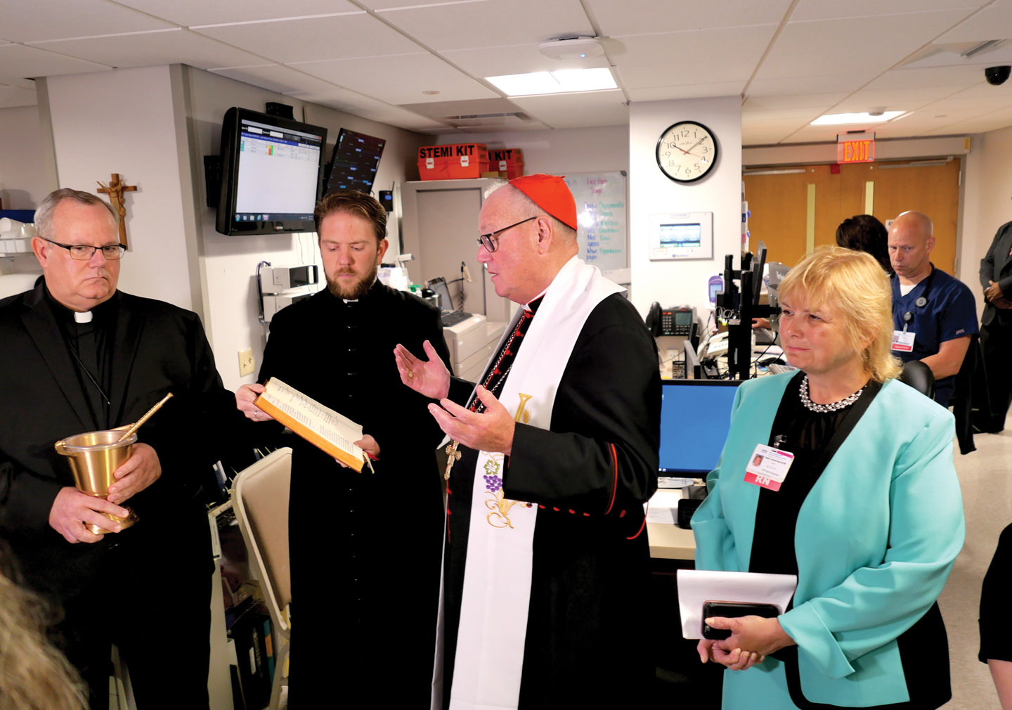 Cardinal Dolan leads prayers during the blessing and dedication of a new temporary emergency department at Bon Secours Community Hospital in Port Jervis Aug. 28. At far right is Sophie Crawford-Rosso, vice president, hospital administrator at Bon Secours. At far left is Father Martin Rooney, director of mission for Bon Secours Charity Health System. Next to him is Father Stephen Ries, the cardinal's priest secretary.