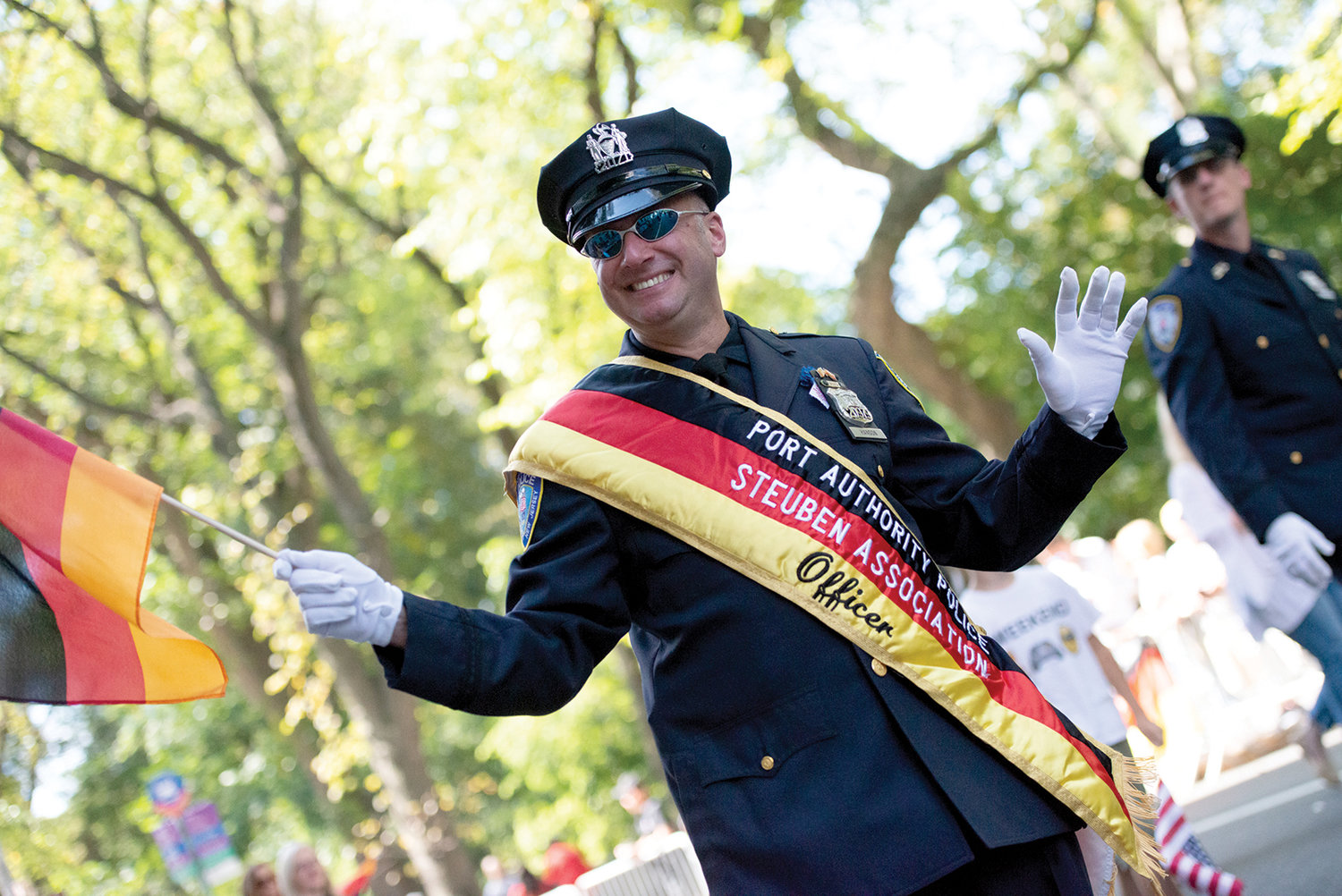 A Port Authority police officer wears a sash matching the colors of the German flag he's waving.