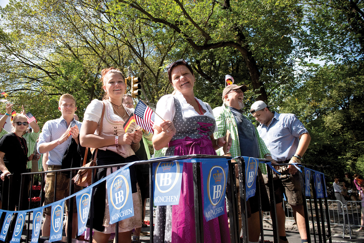 Two women dressed in a dirndl, the ruffled apron dress traditionally worn by German women, stand on a float waving flags of the United States and Germany.