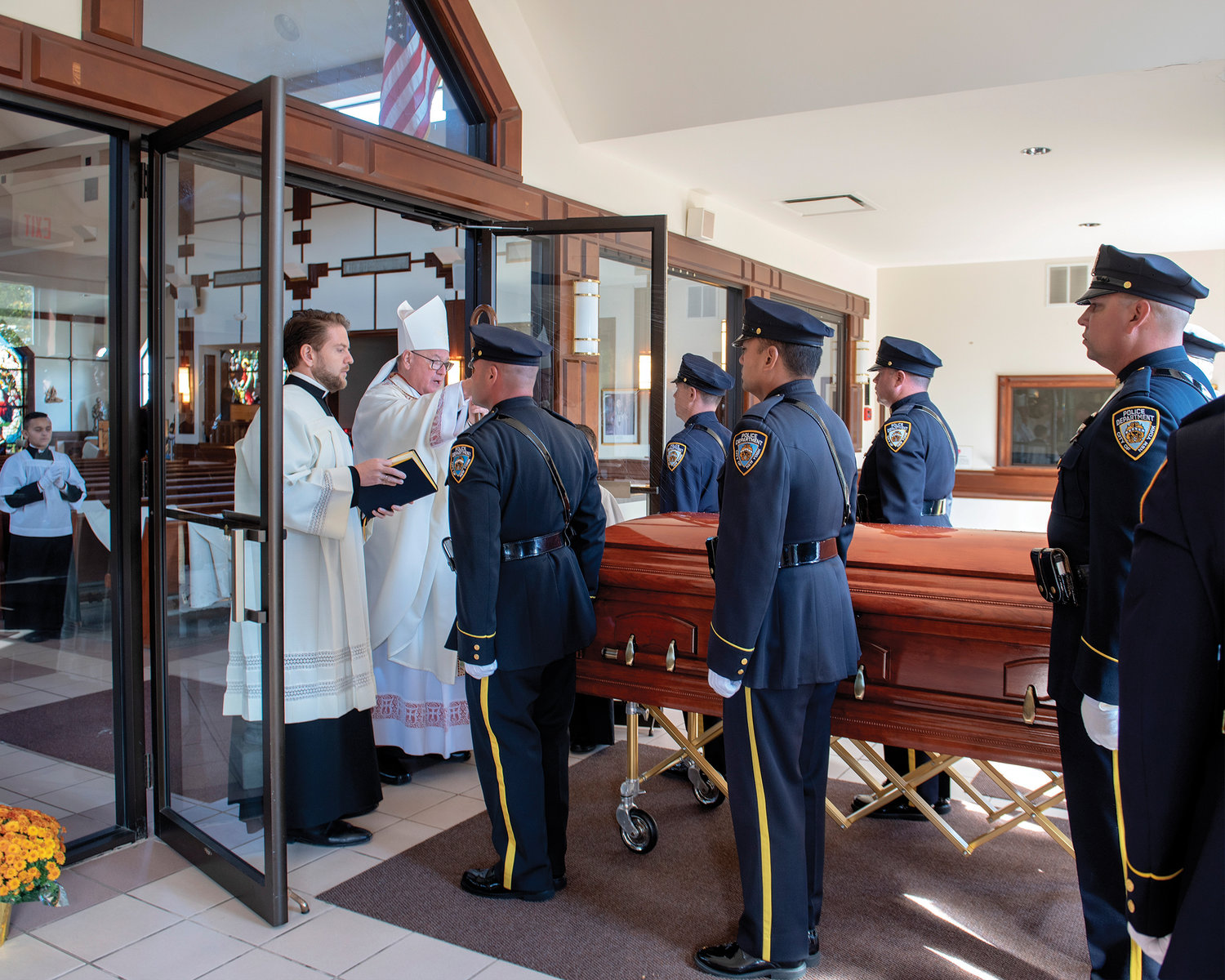 Cardinal Dolan blesses the casket of NYPD Officer Brian Mulkeen at Sacred Heart Church in Monroe Oct. 4, where the cardinal celebrated the Funeral Mass of the 33-year-old officer who died from friendly fire in the line of duty in the Bronx. At the cardinal's side is his priest secretary, Father Stephen Ries.