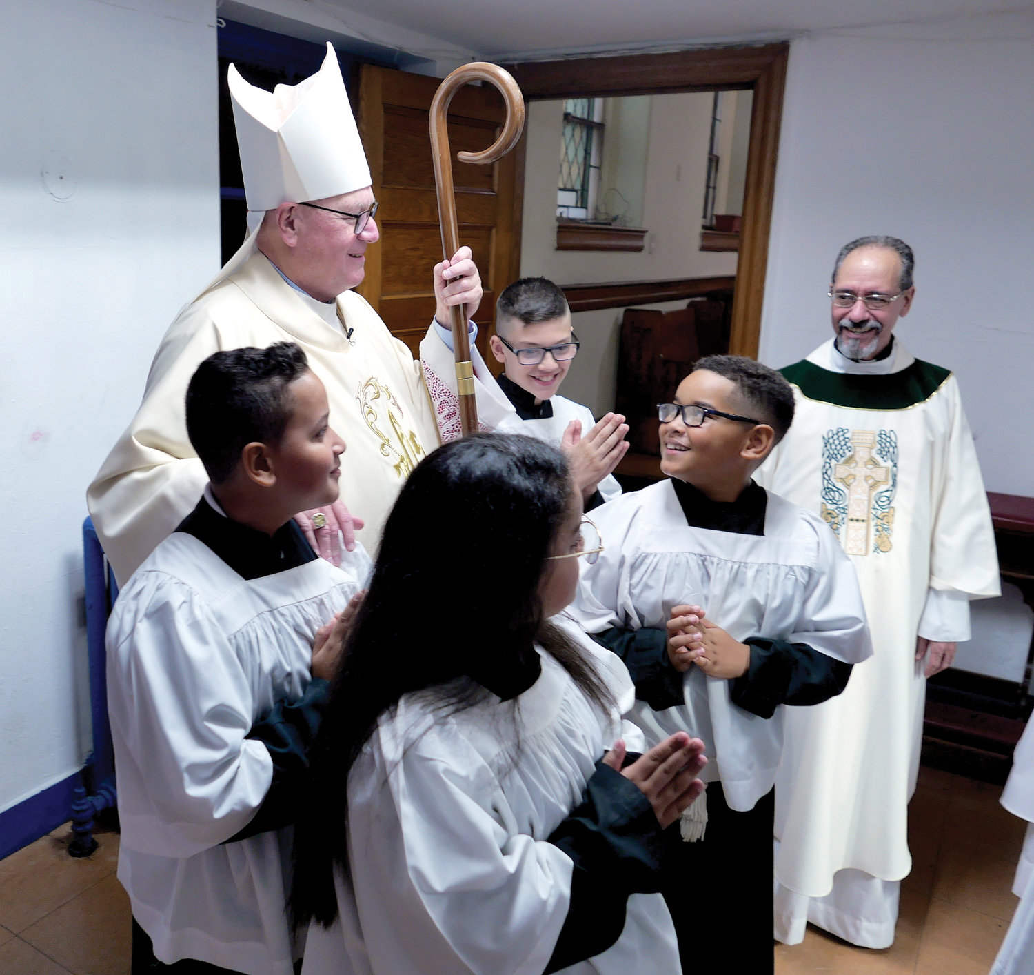 Cardinal Dolan meets with altar servers and Father Osiris Salcedo, S.D.B., administrator of St. Luke parish in the Bronx, before the start of Mass celebrating the 100th anniversary of St. Luke School Oct. 2.