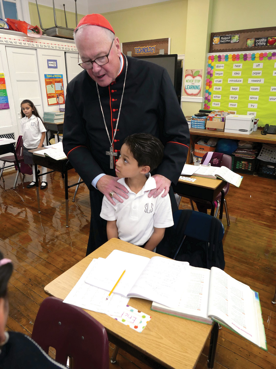 Cardinal Dolan visits with third-grader Erik Valle during his tour of the school.