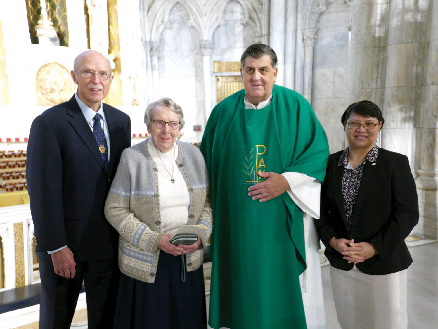 Msgr. Marc Filacchione, director of the archdiocesan Office of the Society for the Propagation of the Faith, greets Brother David Cooney, F.M.S., Sister Margaret Rogers, S.H.C.J, and Lourdes Victoria of the Propagation office staff after the World Mission Sunday Mass at St. Patrick's Cathedral Oct. 20. Brother Cooney and Ms. Victoria were the lectors, and Sister Margaret offered the prayers of the faithful at the Mass.