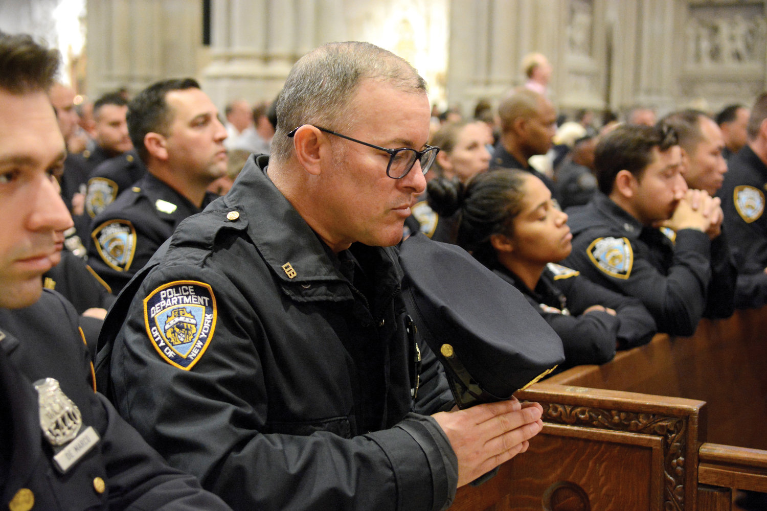 Police officers bow their heads in prayer during the Oct. 13 Mass in St. Patrick's Cathedral at which Cardinal Dolan remembered fellow NYPD officers who have lost their lives to suicide in recent months.