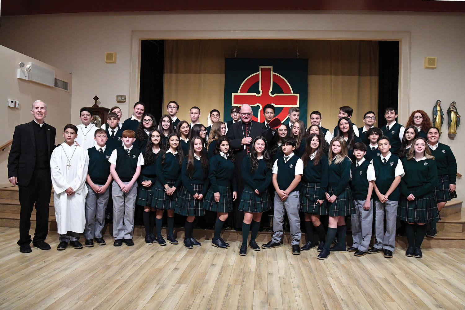 Eighth-graders gather with Msgr. Conway and Cardinal Dolan for a photo after the Mass. The liturgy was attended by the current principal, Vincent Sadowski, and three former principals, as well as teachers, students and other members of the school community. The school was served by the Sisters of St. Dorothy, and members of that congregation were also present.