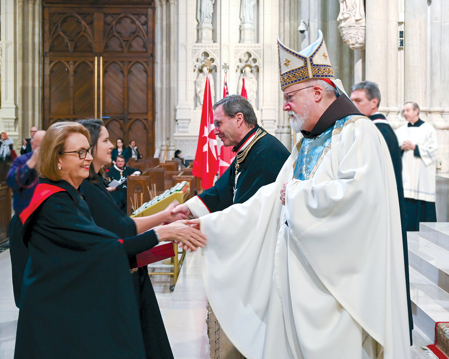 Peter J. Kelly, president of the American Association of the Order of Malta, presents the insignia cross of the order to newly invested dames during the Solemn Liturgy of Investiture Nov. 15 at St. Patrick's Cathedral. Boston Cardinal Séan O'Malley, who served as principal celebrant and homilist, offers congratulations.
