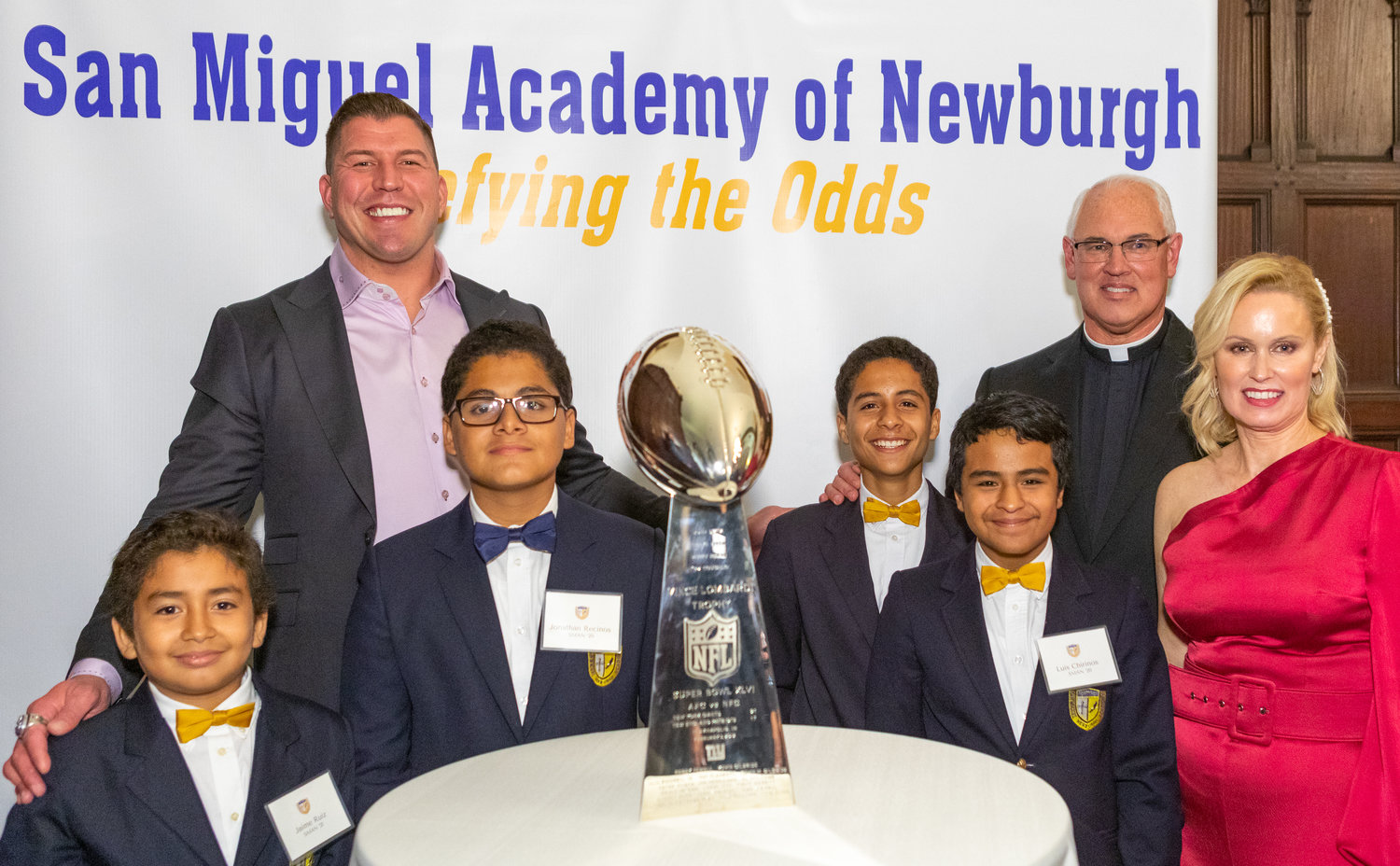 WINNING SMILES—At the Defying the Odds dinner Oct. 25 were former New York Giants player David Diehl; students Jamie Ruiz, Christopher Recinos, Jonathan Recinos and Luis Churinos; Father Mark Connell, executive director of San Miguel Academy; and honoree Ann Mara Cacase. The Vince Lombardi trophy is from the Giants' win in Super Bowl XLVI in 2012.