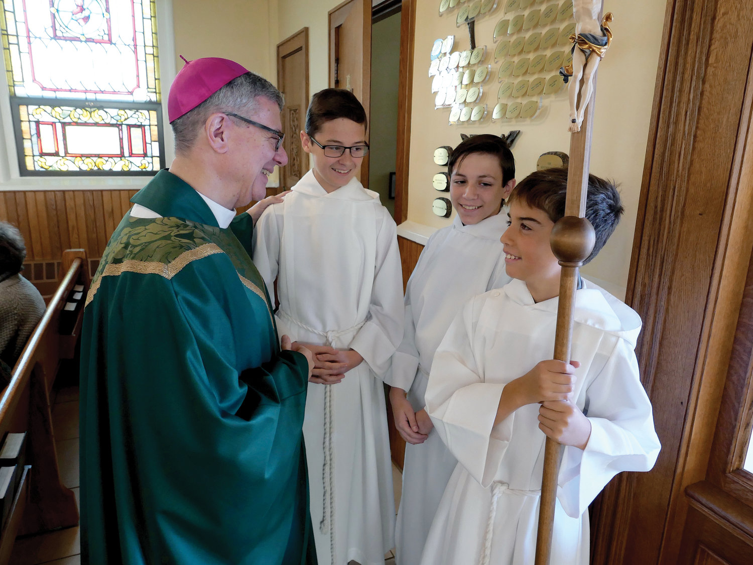 Bishop-elect Gerardo Colacicco shares a smile with altar servers, from left: Andrew Clegg, Liam Canevari and Jacob Zmudosky in the back of St. Joseph-Immaculate Conception Church in Millbrook Nov. 3.