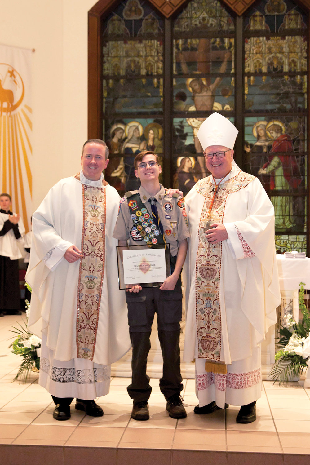 Sean Mende, 17, joins Father David Rider, parish administrator at Sacred Heart in Monroe, and Cardinal Dolan after the Nov. 24 Mass celebrating the Feast of Christ the King and recognizing the transfer of the tabernacle that served as Sean's Eagle Scout project. Sean is holding a certificate of appreciation from the parish.
