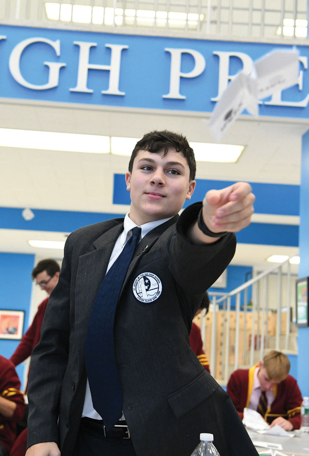 Frank Falcone, a student at St. Joseph by-the-Sea, sends his paper airplane soaring on a test flight.