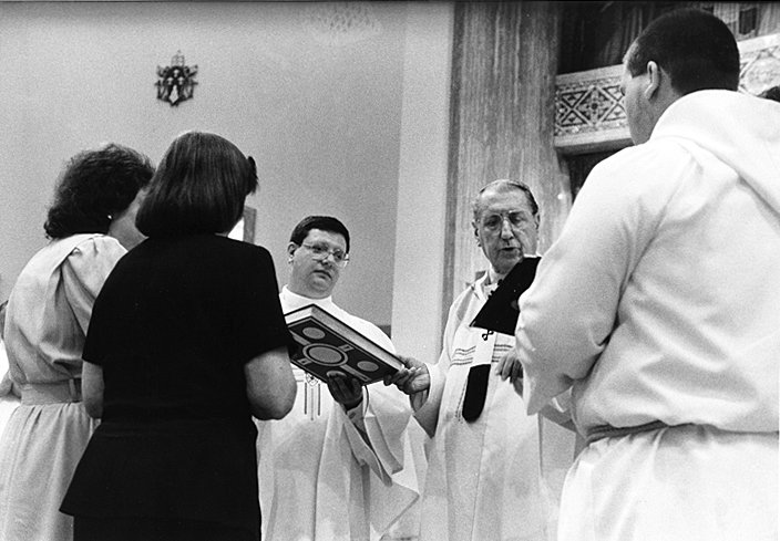 PRIESTLY SERVICE—Cardinal John O'Connor, right, holds Book of the Gospels with Father Gerdardo Colacicco, who he installed as pastor of Sacred Heart parish in Newburgh June 29, 1996.