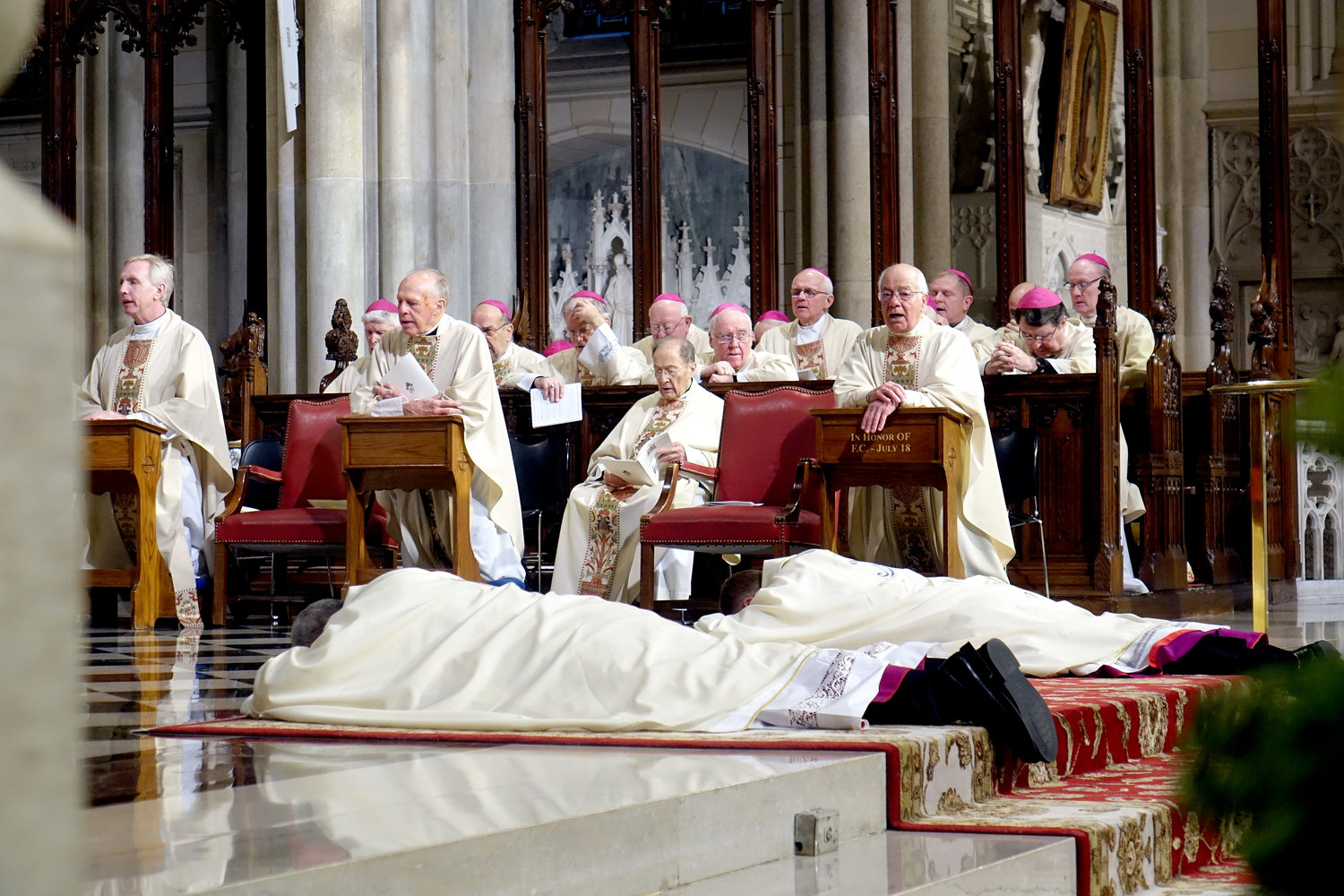 Auxiliary Bishop Gerardo J. Colacicco and Edmund J. Whalen lay prostrate in the sanctuary during the Rite of Ordination. Their assisting priests, from left, Father Robert Dillon, Msgr. Thomas Bergin, Msgr. John Ruvo and Father Richard LaMorte, are seated in front of concelebrating prelates.