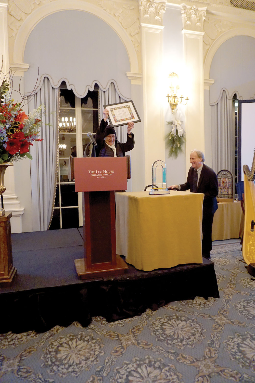 Mother Dolores Hart, O.S.B., raises the certificate for the Pope Leo XIII Award she received from the Leo House, a Catholic guesthouse in Manhattan, at its third annual fund-raising gala named for the pontiff.