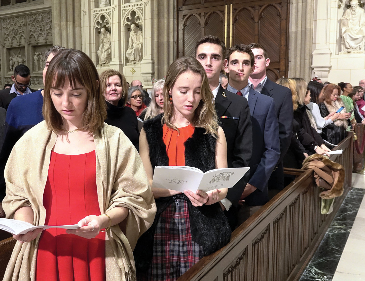 The faithful, assembled in the pews, participate in the liturgy commemorating the Nativity of the Lord.