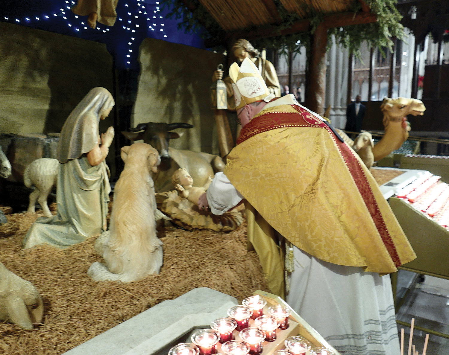 Cardinal Dolan carefully lays a statue of the Infant Jesus into the Nativity manger before blessing the Christmas crèche at the Christmas Midnight Mass he celebrated at St. Patrick's Cathedral Dec. 25.