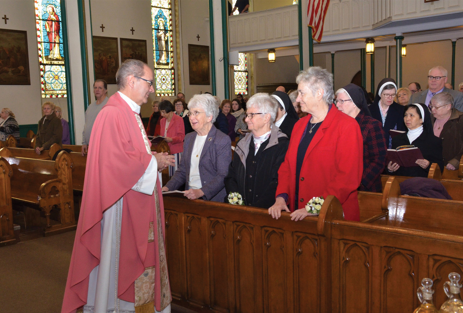 Father William Scafidi, pastor of St. Mary's-St. Peter's parish, greets Sister Mary Feehan, O.S.B., prioress of the Benedictine Sisters; Sister Gabrielle Keenen, O.S.B., and Sister Dorothy Huggard, O.S.B.