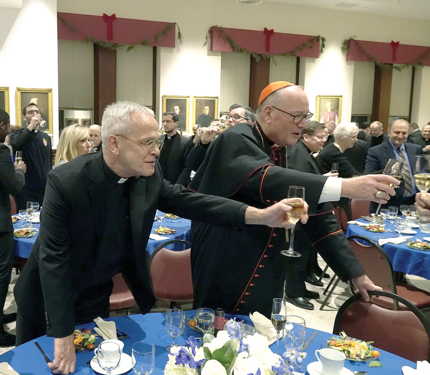 Msgr. Peter Vaccari, rector of St. Joseph's Seminary in Dunwoodie, and Cardinal Dolan extend their glasses during a toast at a farewell gathering for Msgr. Vaccari Dec. 18 at the seminary.