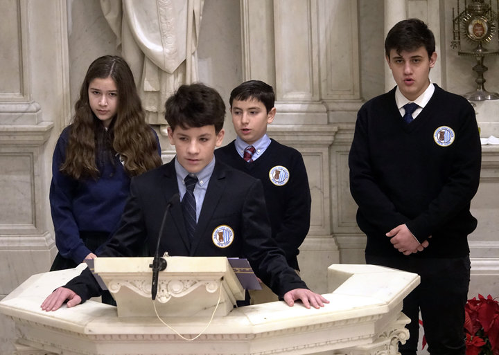 CATHOLIC SCHOOL PRESENCE—High school students, from left, Lena Sidell, of Dominican Academy in Manhattan, and Alexander Jaffres-Bell, Michael McGreal and Daniel Arco, all of Xavier High School in Manhattan, offered the Prayer of the Faithful at the Jan. 4 Mass in St. Peter's Church honoring St. Elizabeth Ann Seton.
