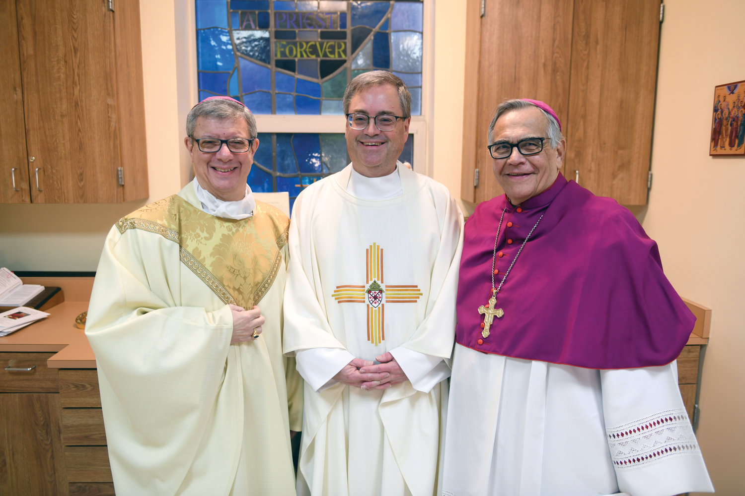 Auxiliary Bishop Gerardo Colacicco, a former pastor of St. Columba, Hopewell Junction, Father Michael McLoughlin, the current pastor, and retired Auxiliary Bishop Dominick Lagonegro, also a former pastor of the parish, gather in the sacristy before the Jan. 5 Mass of Thanksgiving Bishop Colacicco celebrated at St. Columba Church.