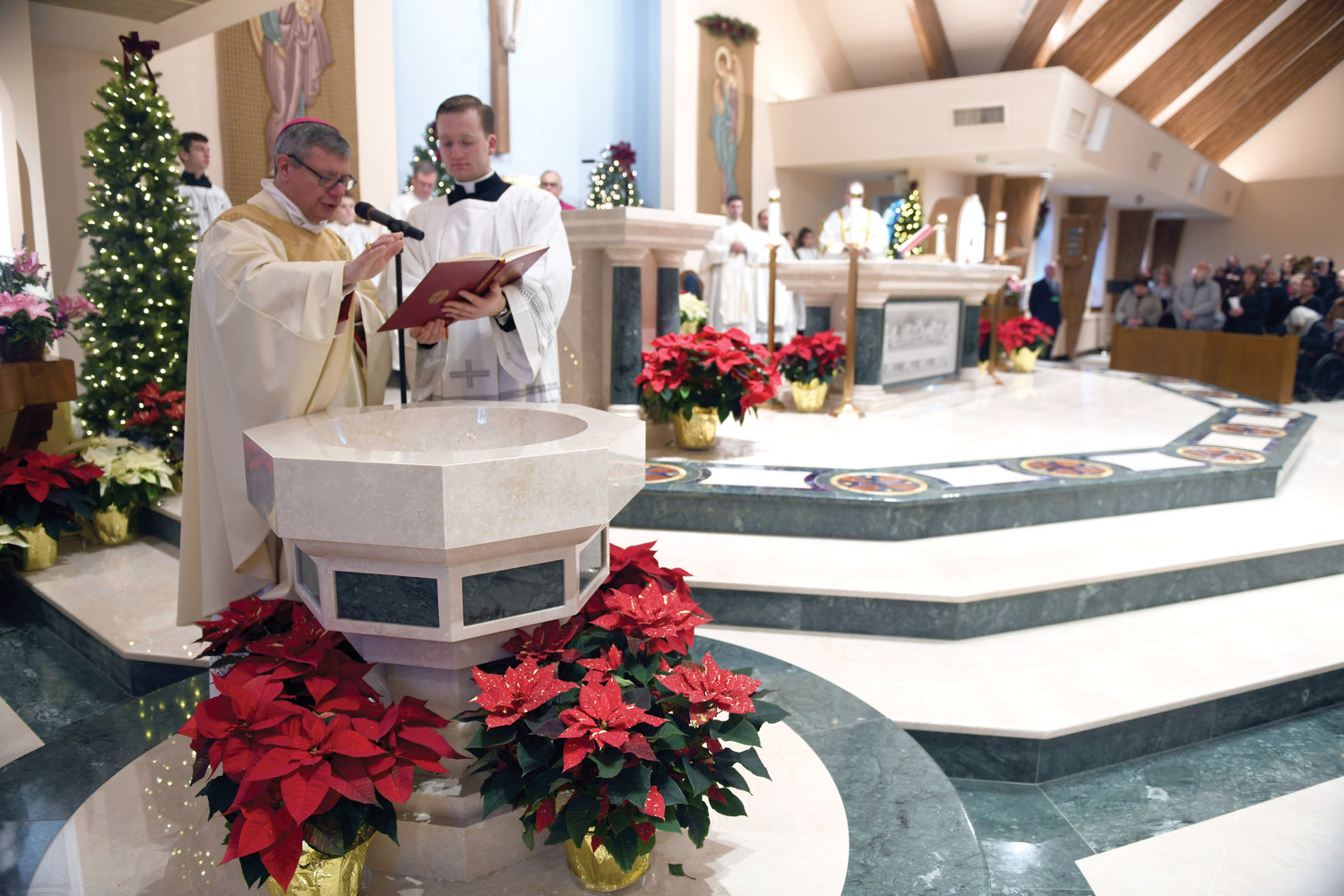 Bishop Colacicco blesses the baptismal font. To his right is Father Michael Connolly, parochial vicar of St. Columba's.