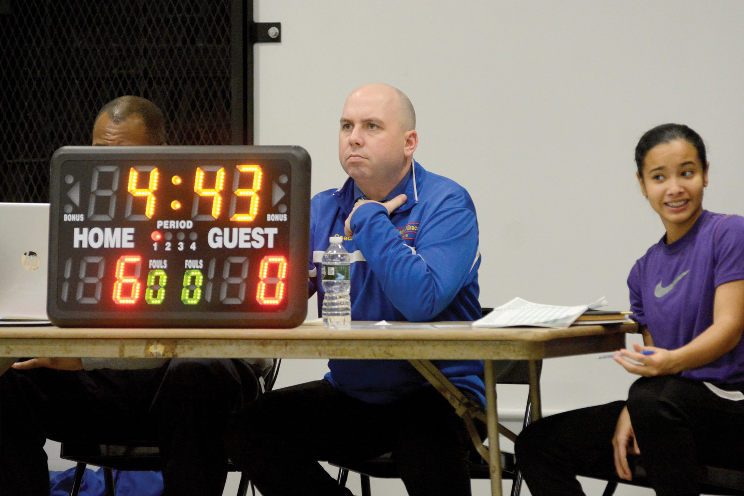 Principal Rich Helmrich operates the scoreboard at the scorer's table.