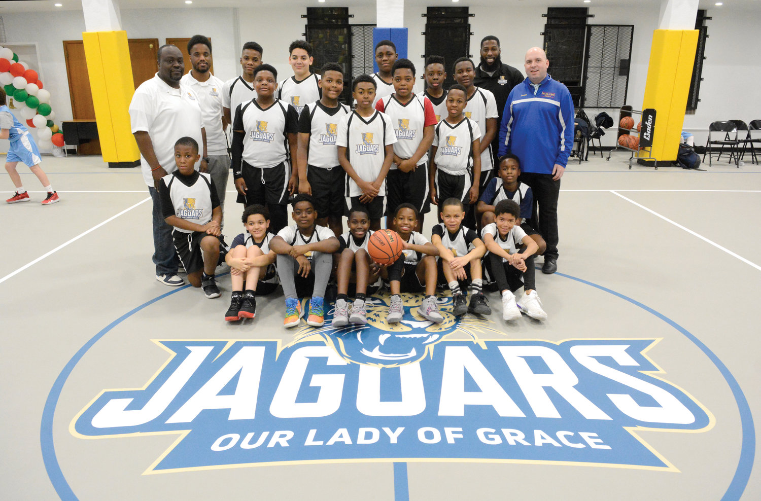 TEAMWORK—Coaches and players from the fifth- and sixth-grade and seventh- and eighth-grade boys' teams at Our Lady of Grace School in the Bronx gather around the school's Jaguars logo at center court with principal Rich Helmrich, far right, in the school's new gymnasium in the Bronx Jan. 8.