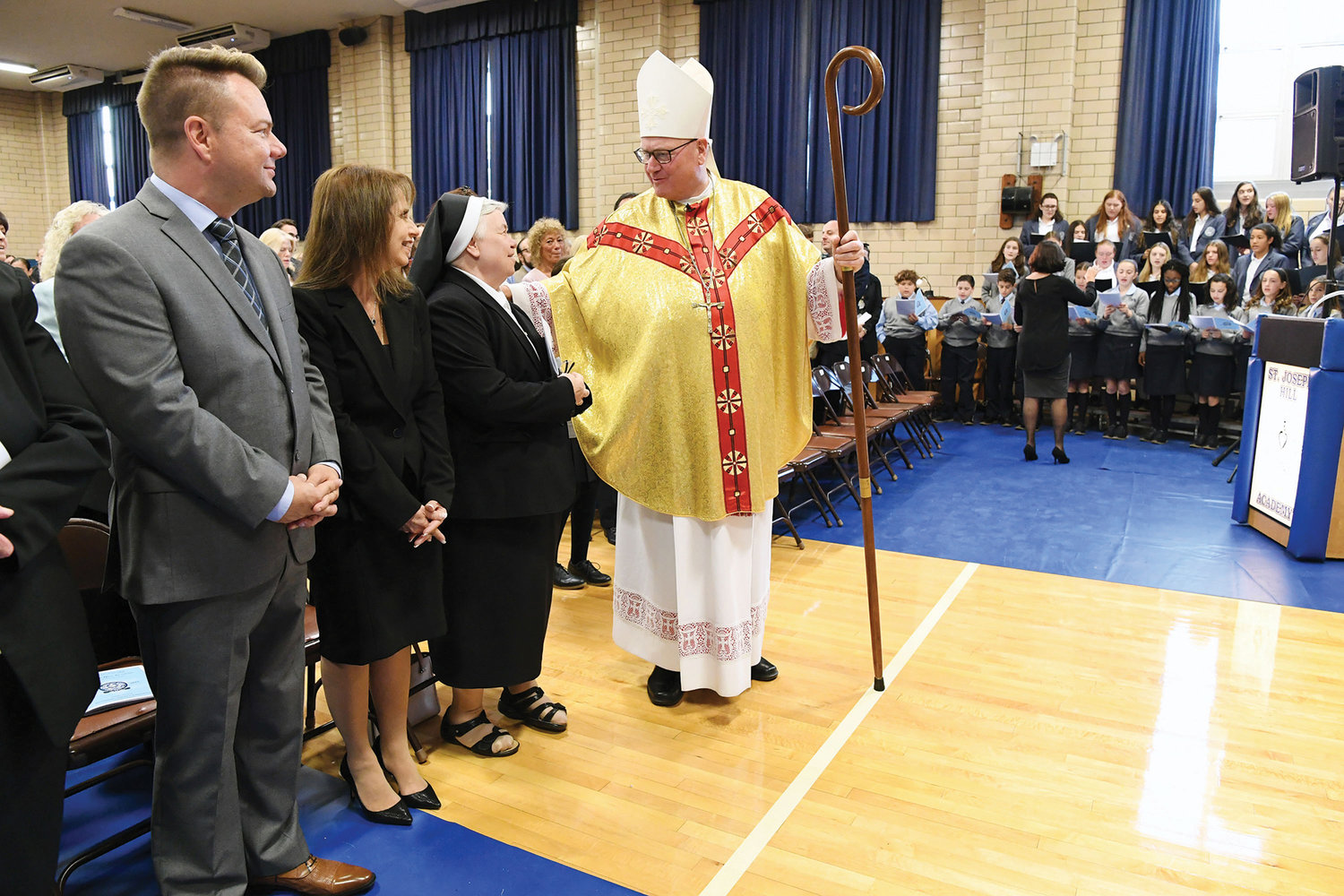 Cardinal Dolan greeted Sister Mary Coffelt, F.D.C., provincial superior and school president, as he processed to the altar. To the left are Lawrence Hansen, principal of the elementary school and Maria Molluzzo, high school principal.