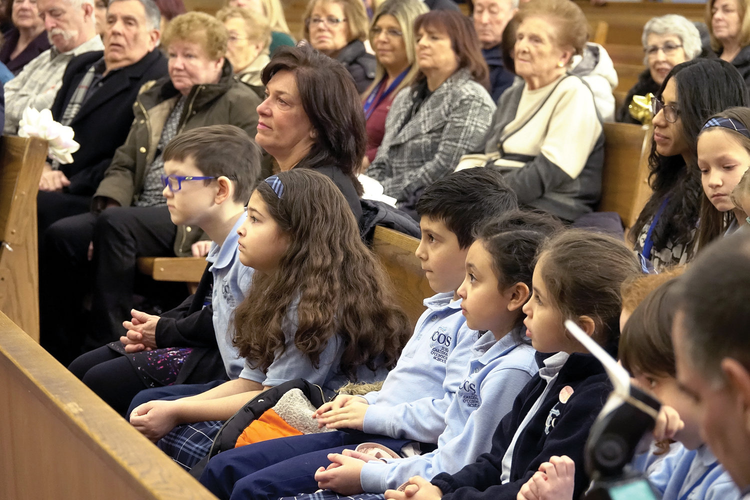 Students, other members of the school and guests attend Mass Cardinal Dolan offered at Immaculate Conception Church before he toured the school and attended a reception there.